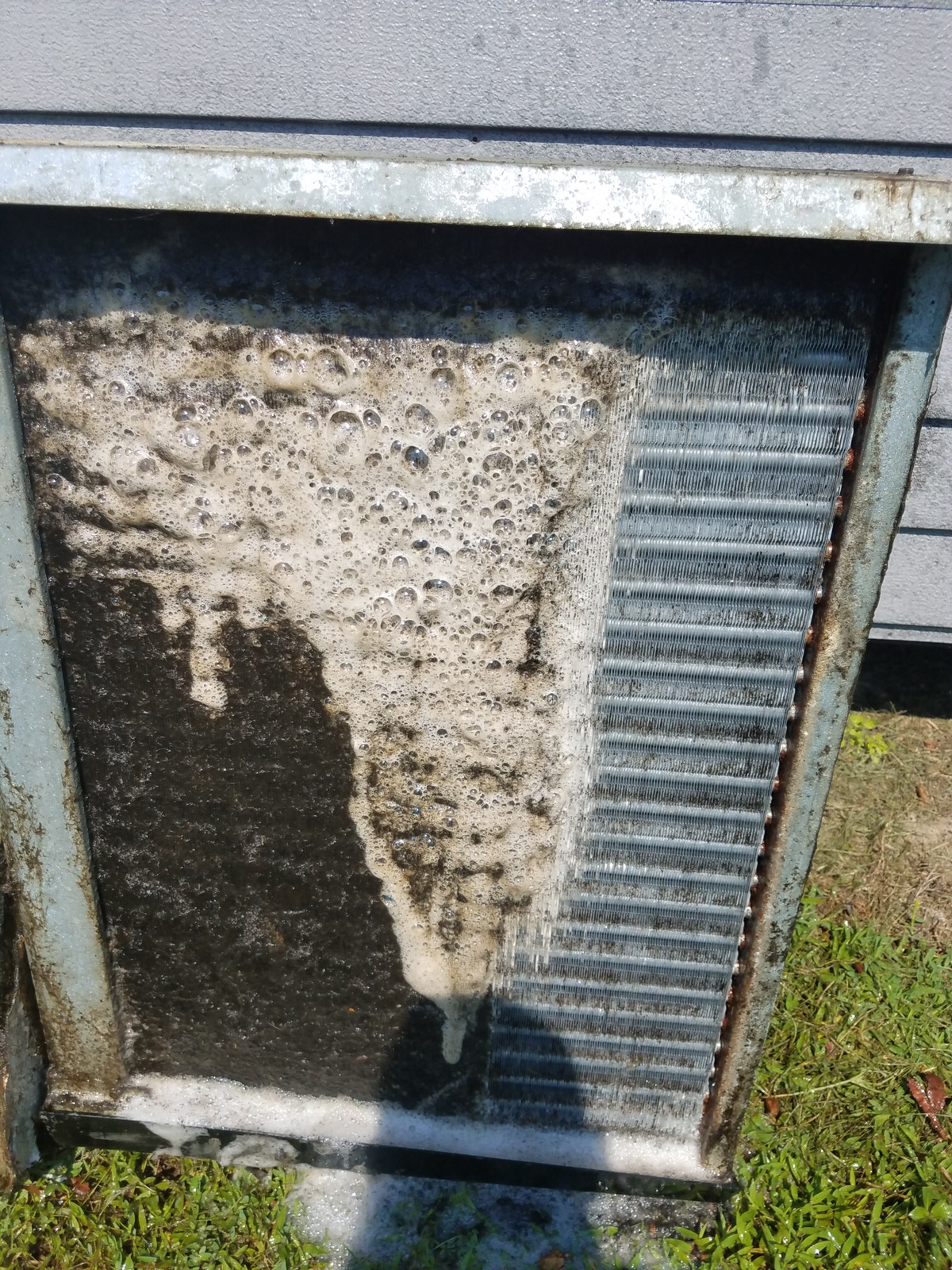 Evaporator coil being cleaned with foamy cleanser - before cleaning on the left, after cleaning on the right